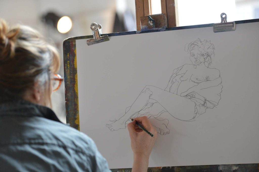A lady drawing a figure seated at an an easel in Porthmeor Studios. St Ives. Life Drawing class.